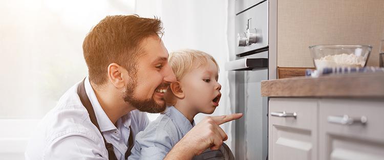 Vater und Sohn schauen in Backofen