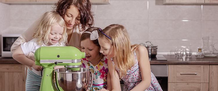 Frau backt in der Küche zusammen mit drei Kindern
