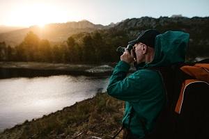 Wetterbedingungen bei Naturfotografie: Mann fotografiert Sonnenaufgang in den Bergen