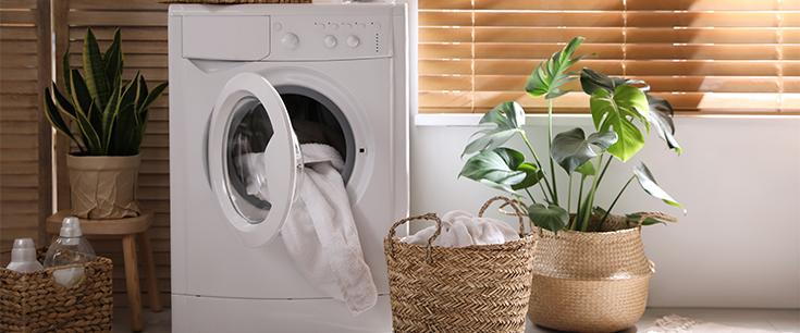 Weiße Waschmaschine die im Badezimmer steht, gefüllt mit Wäsche