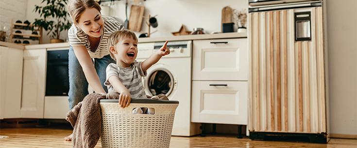 Frau schiebt Sohn in Wäschekorb lachend über den Küchenboden