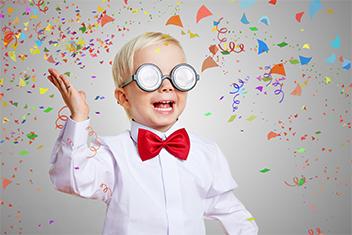 Kind mit Brille auf das Konfetti wirft